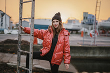 Young Stylish Woman In A Red Down Jacket And Hat On City Street In Industrial Park