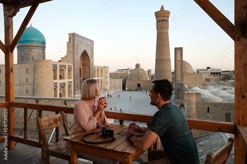 Obraz Tourist Man Woman Drink Coffee on Mosque View - fototapety do salonu
