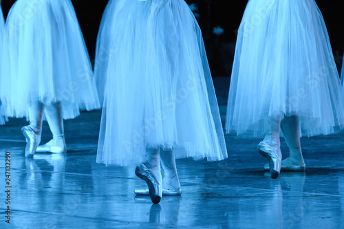 Group of ballerinas in white Chopin tutu synchronized dancing on stage. View from behind.  Ballet dancers on stage performing classical dance. Dancers in the movement. Feet of ballerinas close up