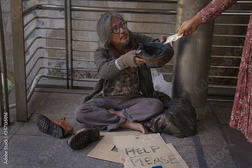 Fotografie, Obraz  Homeless man is sitting down on walkway in town
