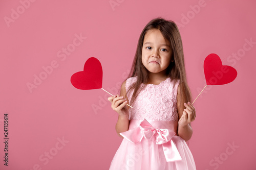 7faaa3ca25d5 portrait of sad cute little girl in pink dress holding two paper heart on  pink background