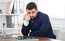 Tired Young Businessman Sitting On Workplace In Office