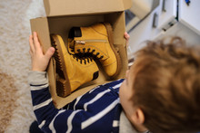 Topview Of A Boy Holding A Open Cardboard Box With A Pair Of Yellow Leatrher Boots