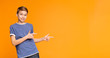Cute little boy pointing away on orange background
