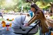 canvas print picture - Junge Mutter ist mit ihrem Baby im Kinderwagen draussen auf dem Spielplatz