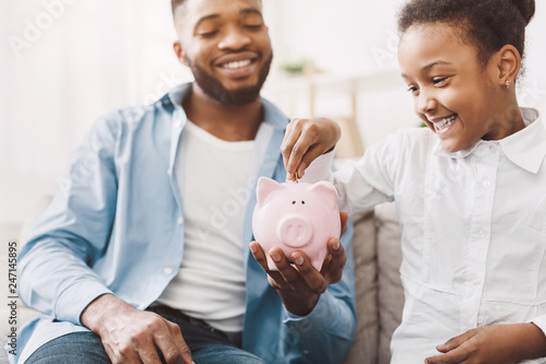 Photo Little african-american girl saving money to piggybank