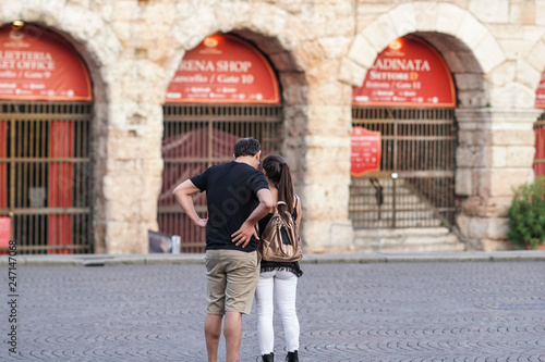 Photo sur Aluminium Con. Antique Back turned unrecognizable couple of tourists outside the Verona Arena, a Roman amphitheatre in Piazza Bra in Verona, Italy, built in the first century. Selective focus