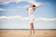 slender brunette in white clothes jumping in the sandy desert