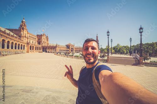 happy smiling man take photo selfie in Spain square (plaza de espana) in Sevilla, Spain