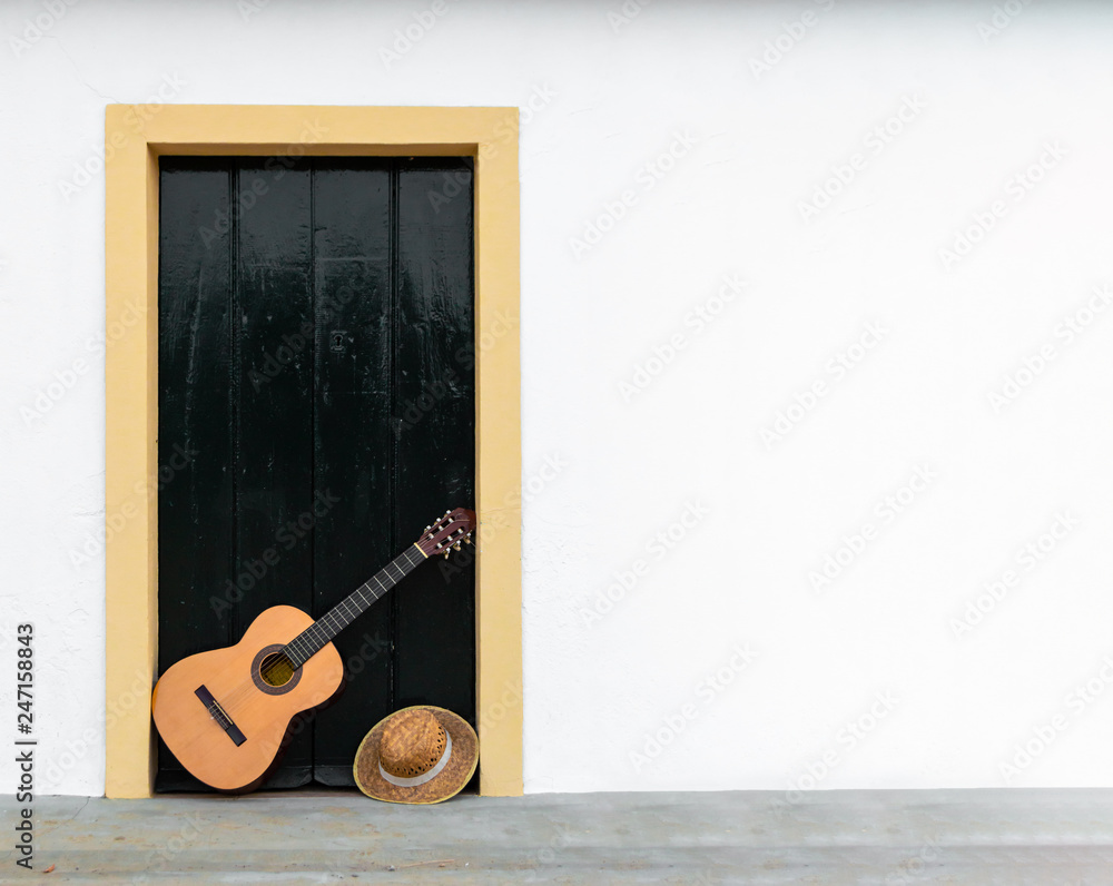 Fototapeta Spanish or classical guitar resting on a door of an andalusian patio, copy space right. Outdoor scene, musical instrument in white wall of rural house.