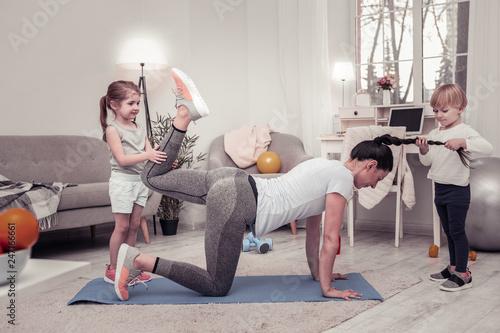 Fotomural  Children disturbing their mother doing morning exercises