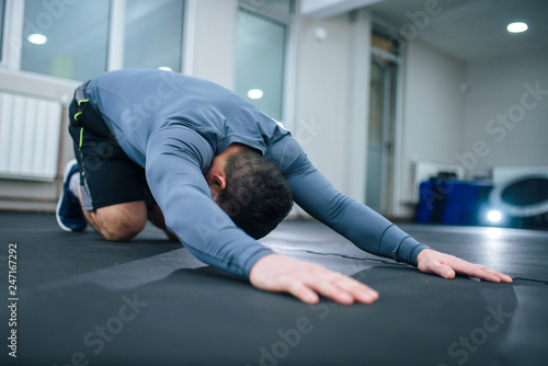Low angle image of muscular man stretching back indoors. Tapéta, Fotótapéta