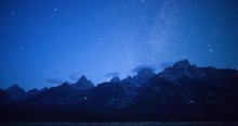 A Time Lapse Of Stars Over The Teton Range In Grand Teton National Park, Wyoming. The Headlamps Of Climbers Can Be Seen Moving Up The Mountains In The Early Morning Hours.