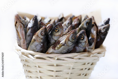 Dried fish to beer close-up in wicker basket
