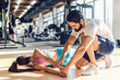 Bearded personal trainer helping woman to stretch arms. Woman lying on mat, gym interior.