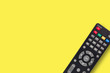 canvas print picture - Single black plastic remote control for different multimedia devices on yellow background with copy space for your text. Top view
