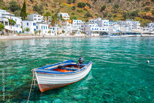 Fishing boat and the scenic village of Loutro in Crete, Greece