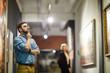 Leinwanddruck Bild - Portrait of pensive bearded man looking at paintings standing in art gallery or museum, copy space
