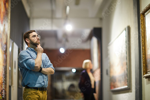 Fotografía  Portrait of pensive bearded man looking at paintings standing in art gallery or