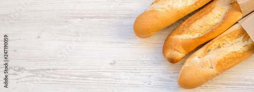 French baguettes in paper bags on white wooden background, overhead view. Space for text.