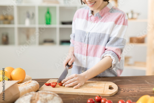 Casual young woman cutting fresh cherry tomatoes on wooden board while cooking breakfast for familt