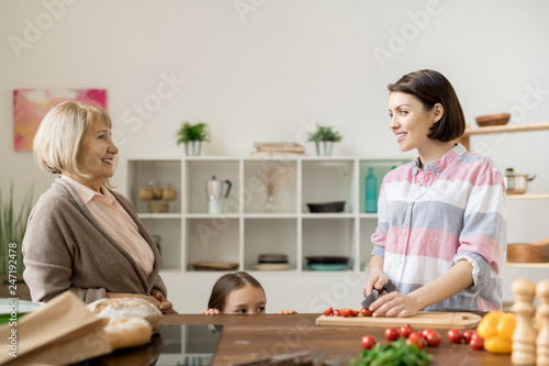 Two casual women having talk in the kitchen while younger one cutting vegetables for salad