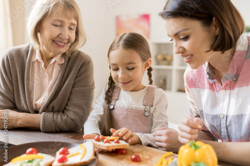 Creative girl making vegetables sandwiches for breakfast among her mother and grandmother