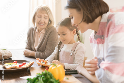 Happy women looking at little girl making sandwiches with fresh vegetables for breakfast