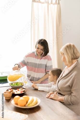 Young woman pouring fresh orange juice from jug into glass by served table during breakfast with her mom and little daughter