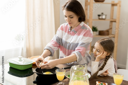 Adorable girl looking at her mom frying eggs while helping her with breakfast in the kitchen