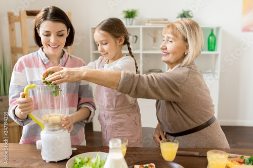 Mature woman and her granddaughter putting fresh green vegetables into blender while preparing smoothie for all family