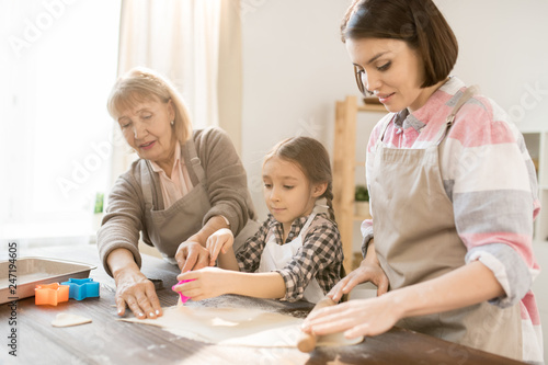 Group of females standing by kitchen table and making homemade cookies while using cutters