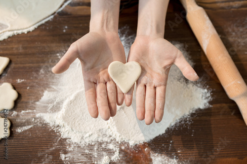 Overview of raw dough in shape of heart on female hands over pile of sifted flour during cooking