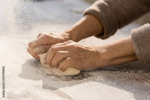 Hands of mature female kneading dough in flour on wooden table before making homemade pastry