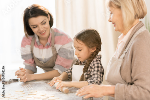 Little girl learning to roll dough and make homemade pastry or cookies with her mother and grandmother