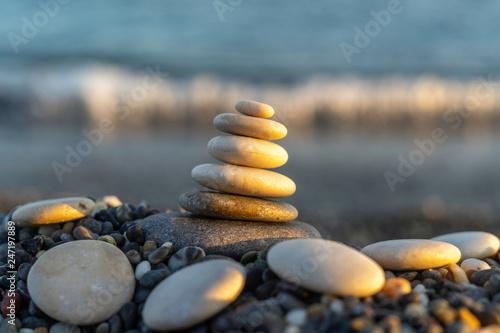 Photo sur Toile Zen pierres a sable Stones pyramid on pebble beach symbolizing stability, zen, harmony, balance. Shallow depth of field.