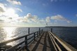 romantic pier with blue sky, fair weather clouds and sunbeams