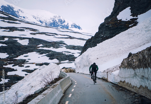 Photo Cyclist on mountain road in Norway, cycling uphill on way after snow avalanche