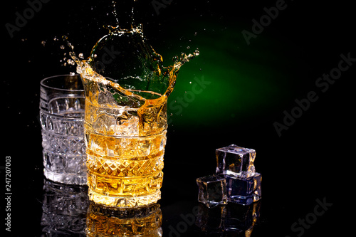 Two crystal glases of whiskey on a beautiful green background and a splash from falling ice