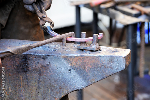 Blacksmith working metal with hammer on the anvil - Buy this stock