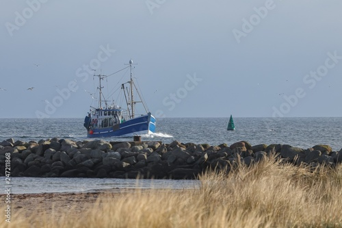 traditional blue fishing vessel enters the harbor