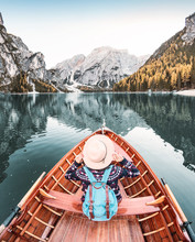 Happy Asian Woman Sitting In Wooden Vintage Boat Floating And Sailing On A Braies Lake In Italian Alps Mountains, Travel And Dream Vacation Concept