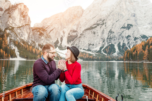 Fotografia  Couple young man and woman together on the boat or canoe cruise tour on well known Braies lake in Italian Dolomites Alps