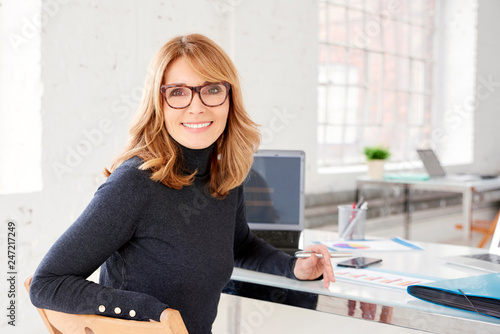 Photo  Confident businesswoman wearing casual clothes while sitting at office and worki