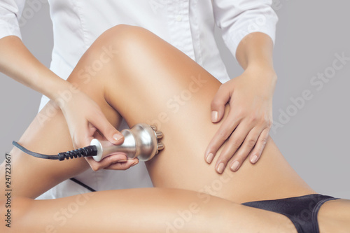 Fotografia, Obraz  The doctor does the Rf lifting procedure on the legs, buttocks and hips of a woman in a beauty parlor