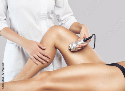 Fotografía  The doctor does the Rf lifting procedure on the legs, buttocks and hips of a woman in a beauty parlor