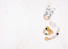 Wooden Toy, Comforter And Teether On Light Marble Background