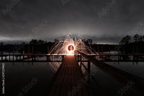 Fotografie, Obraz  Steel Wool Flames over Water at Night