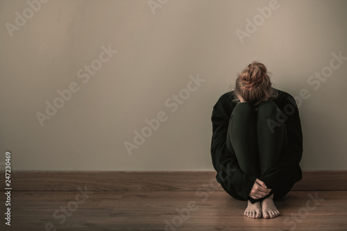 Valokuva  Sad teenager girl sitting curled up on the floor, copy space on empty wall
