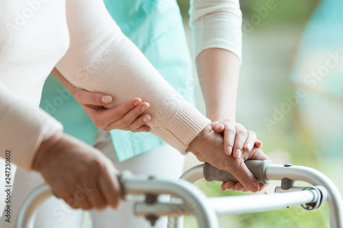 Closeup of elderly lady's hands holding a walker and supporting nurse helping her